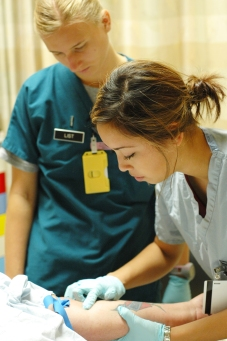 First Lt. Jordan List oversees nursing Cadet Megan King putting in an IV for a patient.