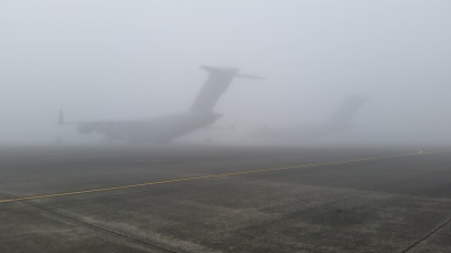 An airfield full of C-17 aircrafts is barely visible on a foggy morning before an aeromedical crew training exercise.