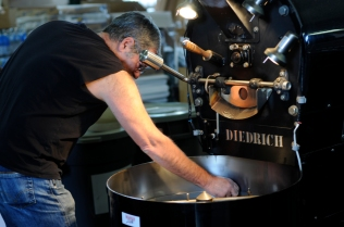 Curtis Black, roast master general for Battle Bean on Joint Base Lewis-McChord, prepares a white coffee blend for a customer..